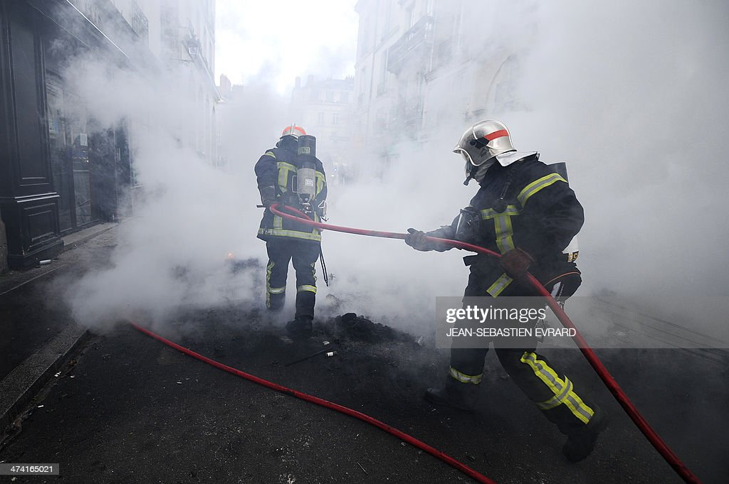 Firefighters put out a fire as protesters clash with French riot police during a demonstration on February 22, 2014, in Nantes, western France, against an international airport project in the French western city of Notre-Dame-des-Landes. The disputed project, signed in 2010, has been put on hold and will likely be postponed beyond the scheduled opening planned for 2017. The planned airport north of Nantes, which is scheduled to replace the city's current airport in 2017, is a pet project of Prime Minister Jean-Marc Ayrault, who was the city's mayor from 1989 to 2013.