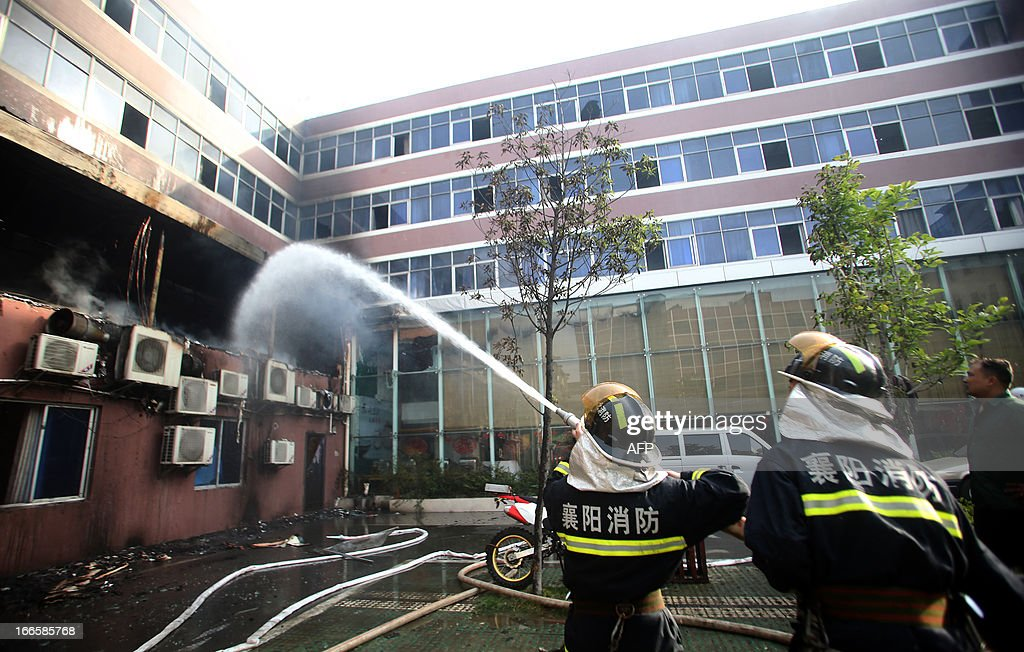 Firefighters put out a fire at a hotel in Xiangyang, central China's Hubei province on April 14, 2013. The fire, started from an Internet cafe downstairs, resulted in 11 deaths and 50 injuries, local government reports annouced. CHINA OUT AFP PHOTO