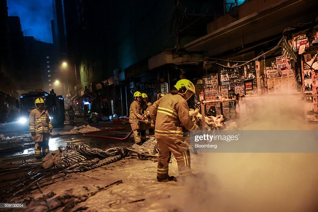 Firefighters put out a fire in the Mong Kok area of Hong Kong, on Tuesday, Feb. 9, 2016. Rioters set fires and threw bricks at police in Hong Kong early Tuesday, injuring officers and shuttering one of the city's busiest subway stations in a clash over illegal food stalls during the three-day Chinese New Year holiday. Photographer: Billy H.C. Kwok/Bloomberg via Getty Images