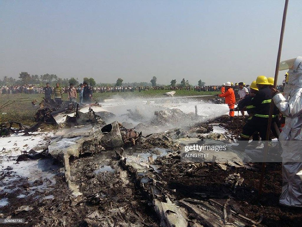 Firefighters put out a fire on the wreckage of a military passenger plane in an agricultural land near the airport in the capital of Nayphidaw on February 10, 2016. Myanmar military personnel were feared dead after a small air force propeller plane crashed shortly after take off in the capital Naypyidaw on February 10, sources said. The Beechcraft passenger plane, which was carrying five crew members and believed to be on a routine patrol, went down in agricultural land near the airport. AFP PHOTO / AUNG HTET / AFP / Aung Htet