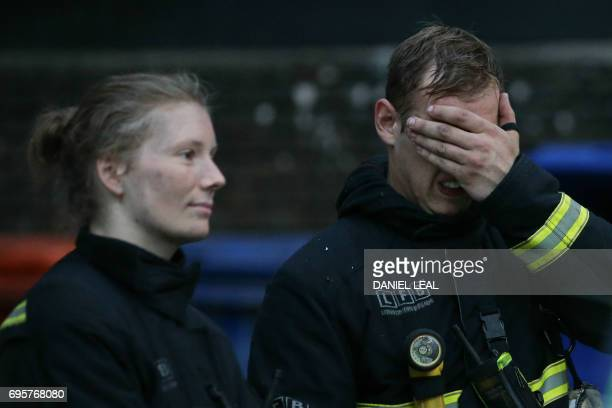 Firefighters react as a huge fire engulfs the Grenfell Tower early June 14 2017 in west London The massive fire ripped through the 27storey apartment...