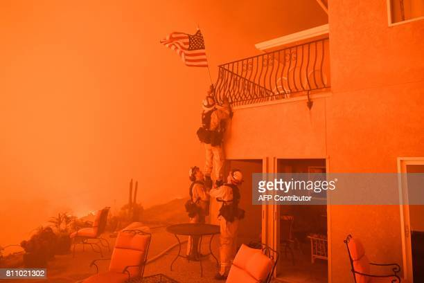 TOPSHOT Firefighters remove a US flag as flames from the 'Wall Fire' close in on a luxury home in Oroville California on July 8 2017 The first major...
