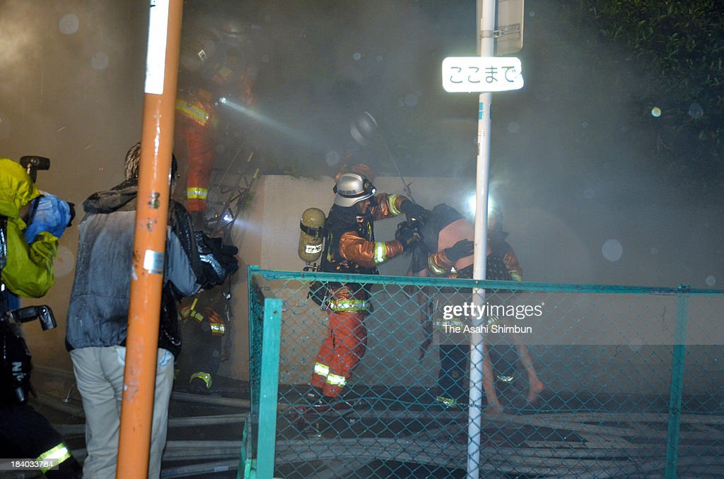 Firefighters rescue a person from a hospital fire site on October 11, 2013 in Fukuoka, Japan. 2 staffs and 8 patients were confirmed dead.