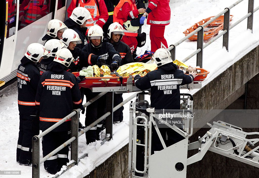 Firefighters rescue an injured passenger at the site where two trains of the line S45 crashed on January 21, 2013 in Vienna, Austria