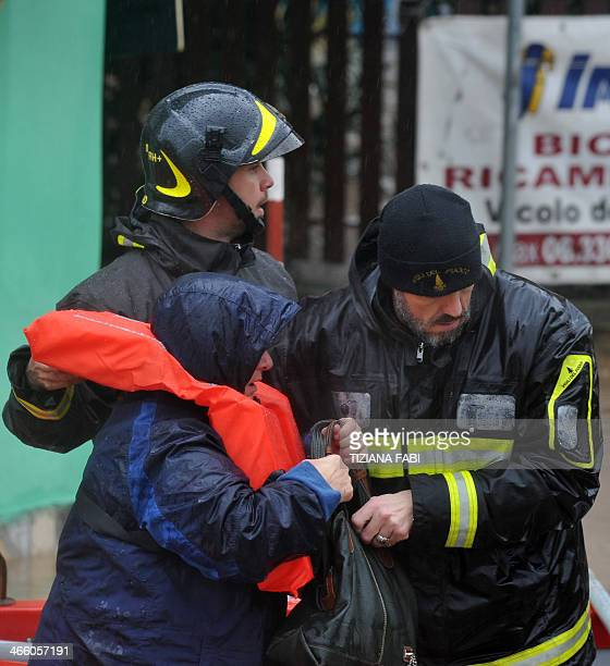 Firefighters rescue people in a flooded street in 'Prima Porta' in the outskirts of Rome after torrential rains hit the region overnight on January...