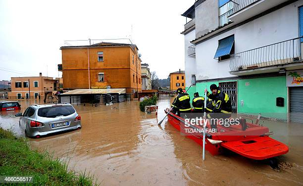 Firefighters rescue people on a small boat in a flooded street in 'Prima Porta' in the outskirts of Rome after torrential rains hit the region...