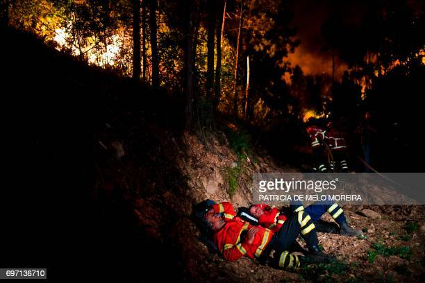 TOPSHOT Firefighters rest during a wildfire at Penela Coimbra central Portugal on June 18 2017 A wildfire in central Portugal killed at least 25...