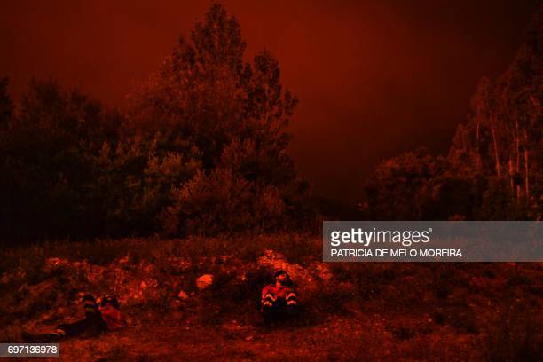 Firefighters rest during a wildfire at Penela Coimbra central Portugal on June 18 2017 A wildfire in central Portugal killed at least 25 people and...