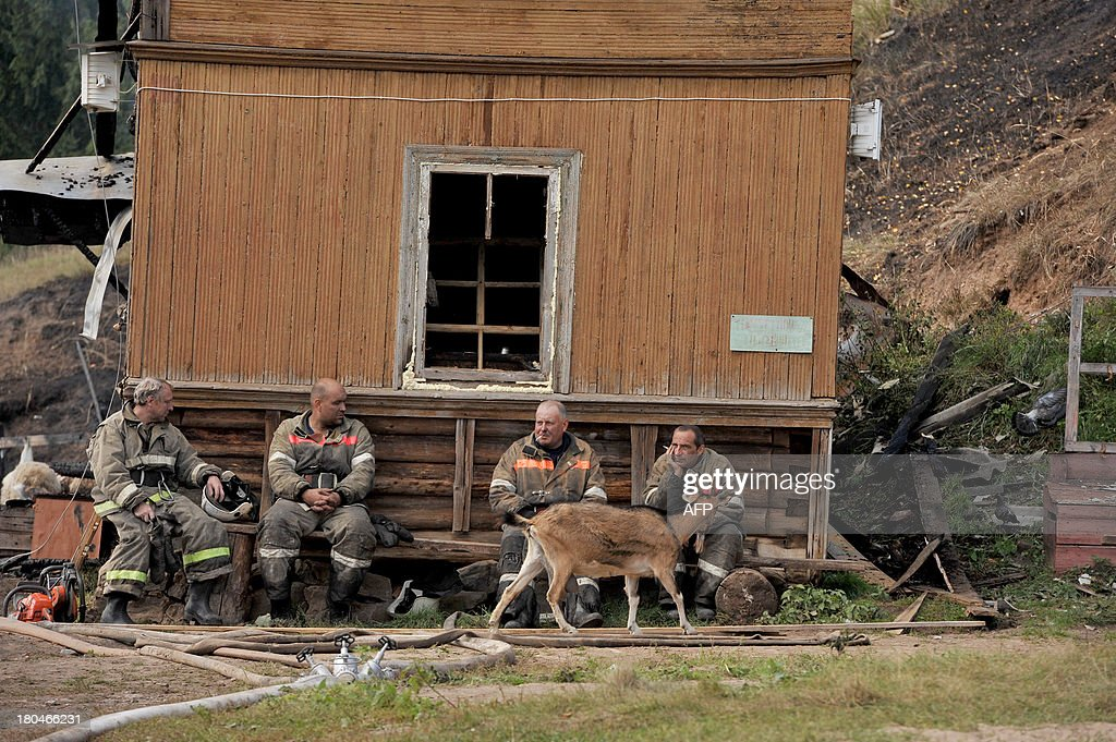 Firefighters rest near the charred remains of the burned out psychiatric hospital in the village of Luka in the northwest Russian Novgorod region, 220 kilometres (137 miles) southeast of Saint Petersburg, on September 13, 2013. Thirty seven people were killed when a fire swept through a wooden psychiatric hospital in northwest Russia overnight yesterday, regional investigators said. AFP PHOTO / OLGA MALTSEVA