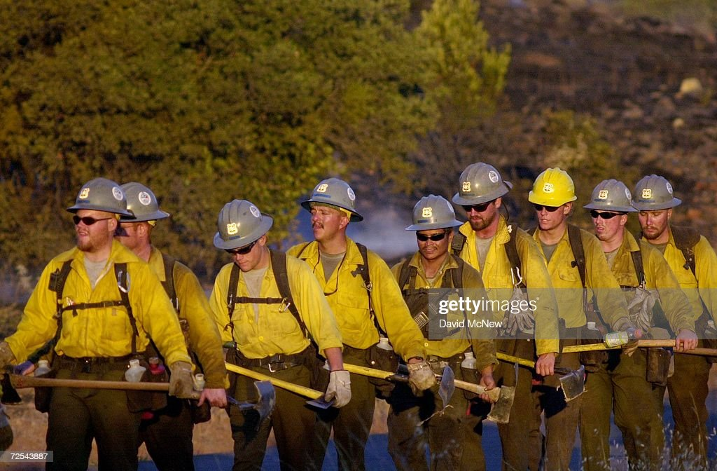 Firefighters return from a successful backfire operation to save houses August 5 2000 at the Pechanga Fire near the Pechanga Indian Reservation...