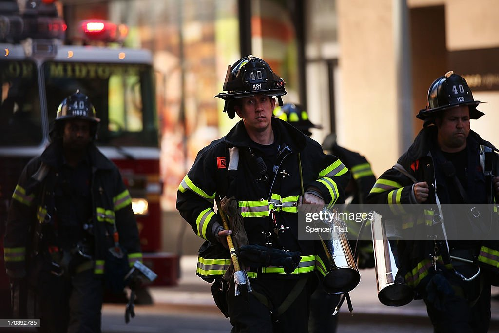 Firefighters return to their trucks after rescuing two window washers left dangling from broken scaffolding on the top of the 46-story Hearst Tower on June 12, 2013 in New York City. The workers, who were servicing the window-washing equipment when the scaffolding broke, were left dangling 500 feet above Eighth Avenue. Firefighters and NYPD emergency service unit officers were were able to rescue the men as hundreds of onlookers gazed up from the street.