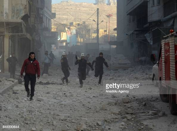 Firefighters run to extinguish a fire at the impact site after Assad Regime's airstrike over civilians in residential areas of Ariha town of Idlib...