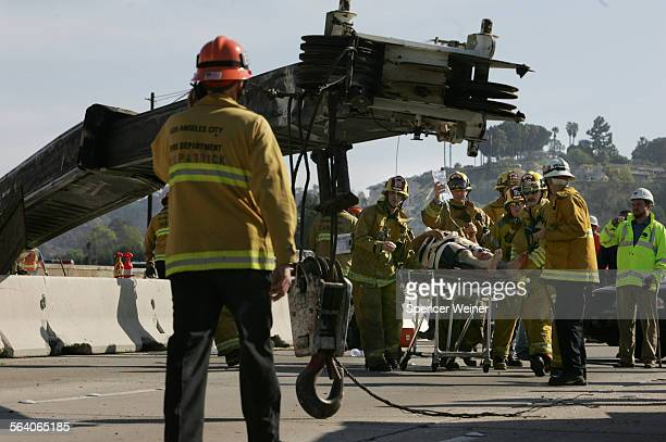 Firefighters rush a crane operator to a waiting life flight helicopter after a giant construction crane he was operating collapsed onto part of the...
