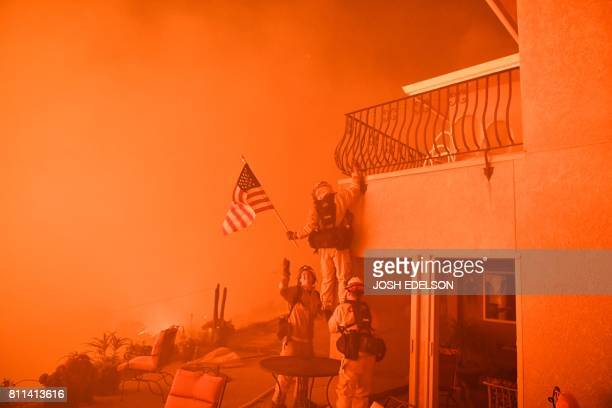 Firefighters save a US flag as impending flames from the Wall fire close in on a luxury home in Oroville California on July 8 2017 At least 10...