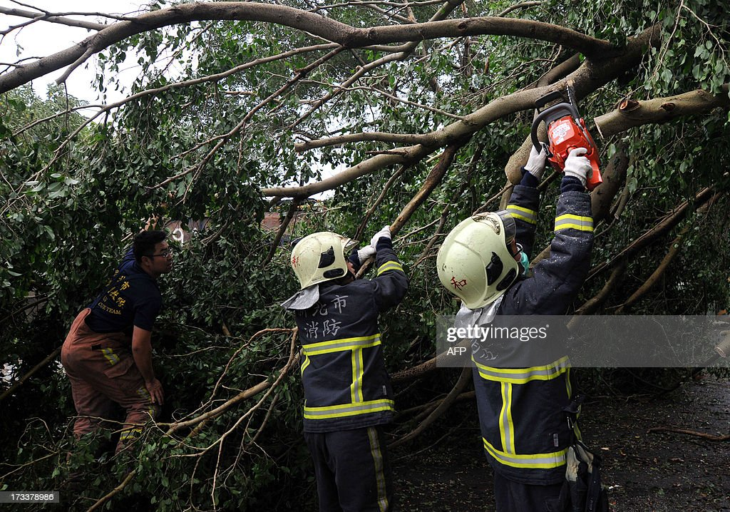 Firefighters saw a damaged tree caused by typhoon Soulik in Taipei July 13, 2013. Thousands of people were evacuated in Taiwan and the entire island declared an 'alert zone' as Typhoon Soulik made landfall early morning, killing one person and injuring seven. AFP PHOTO / Mandy CHENG
