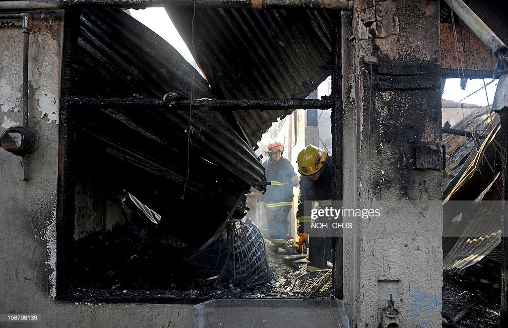 Firefighters search for bodies after a pre-dawn fire engulfed a row of old apartments in Manila on December 25, 2012. At least seven people were killed and thousands left homeless as two fires struck the Philippine capital on Christmas Day, sparking riots as a slum went up in flames, Manila's fire marshal said. AFP PHOTO / NOEL CELIS