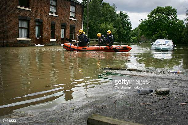 Firefighters search homes in the flooded village of Treeton which has rising floods due to the pumping of water from the Ulley Reservoir where the...