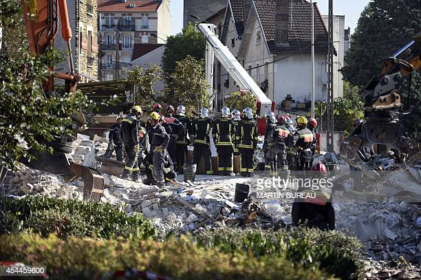 Firefighters search the rubble of a fourstorey residential building which collapsed following a blast on September 01 2014 in RosnysousBois in the...