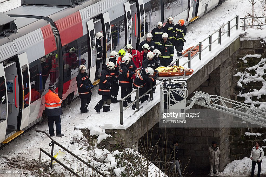 Firefighters secure the site where two trains of the line S45 crashed on January 21, 2013 in Vienna, Austria