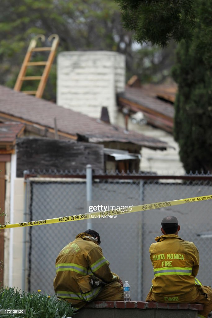 Firefighters sit near a burned house they extinguished before finding two bodies inside after multiple shootings were reported at various locations including Santa Monica College June 7, 2013 in Santa Monica, California. According to reports, at least six people have died in the shootings.