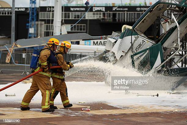 Firefighters spray foam at the scene where a helicopter crashed while installing a large Christmas Tree at the Viaduct Harbour on November 23 2011 in...