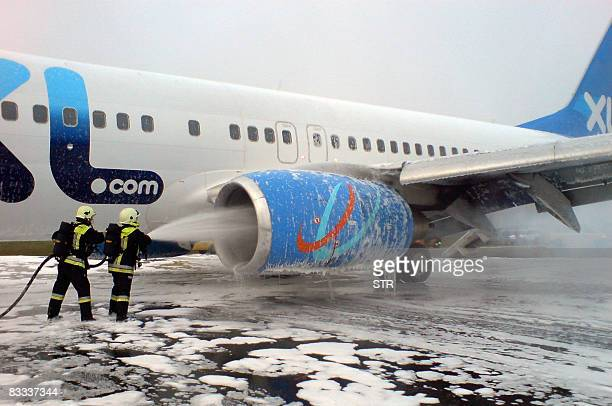 Firefighters spray foam on the engine of a Boeing 737800 airplane of the German company XL Airways on the tarmac of Nikola Tesla Airport in Belgrade...