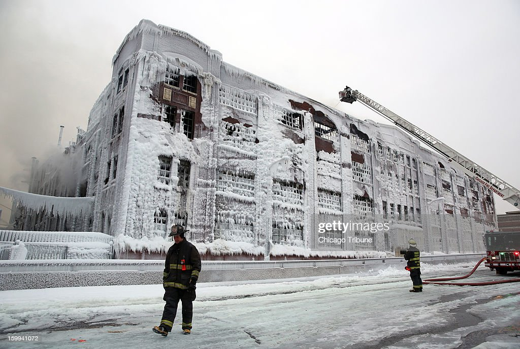 Firefighters spray hot spots remaining from an overnight fire at an abandoned warehouse in Chicago, Illinois, on Wednesday, January 23, 2013.