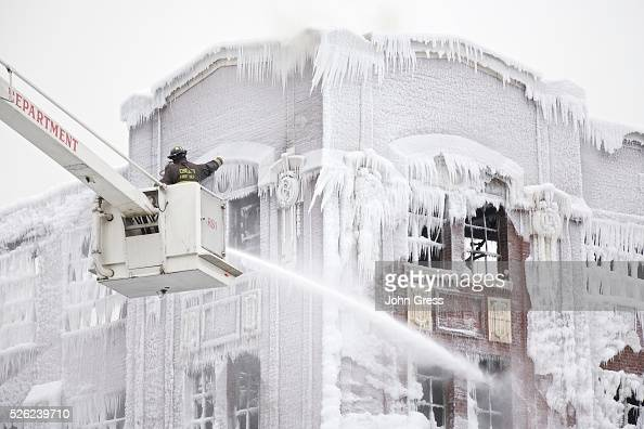 Firefighters spray hotspots on January 23 2013 on an Ice covered warehouse that caught fire Tuesday night in Chicago Fire Department officials said...