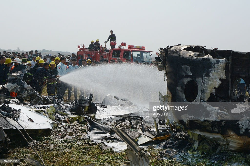 Firefighters spray the wreckage of a military passenger plane which crashed in a field near the airport in the capital of Naypyidaw on February 10, 2016. Four Myanmar military personnel were killed and one was seriously injured after the small air force propeller plane crashed shortly after take off in the capital Naypyidaw, officials said. AFP PHOTO / AUNG HTET / AFP / Aung Htet