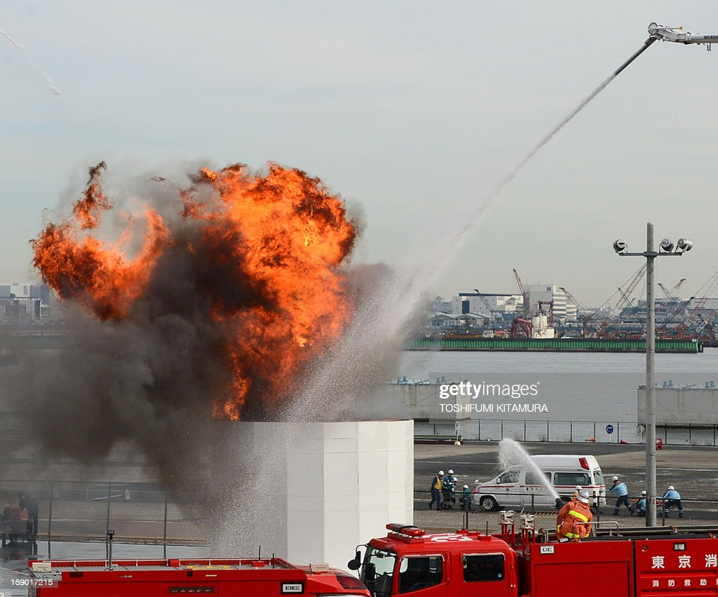 Firefighters spray water during the firefighting demonstration at the annual new year fire review in Tokyo on January 6, 2013. A total of 2,800 fire fighters, 133 vehicles, 5 helicopters and 8 boats participated in the new year firefighting exercises.