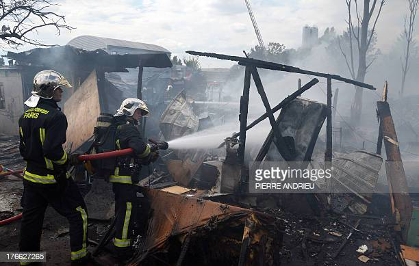 Firefighters spray water with a fire hose at a Roma community campsite destroyed by fire on August 16 2013 in NoisyleGrand a Paris suburb The...