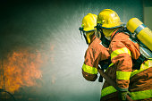 2 firefighters spraying in cinematic tone with copy space