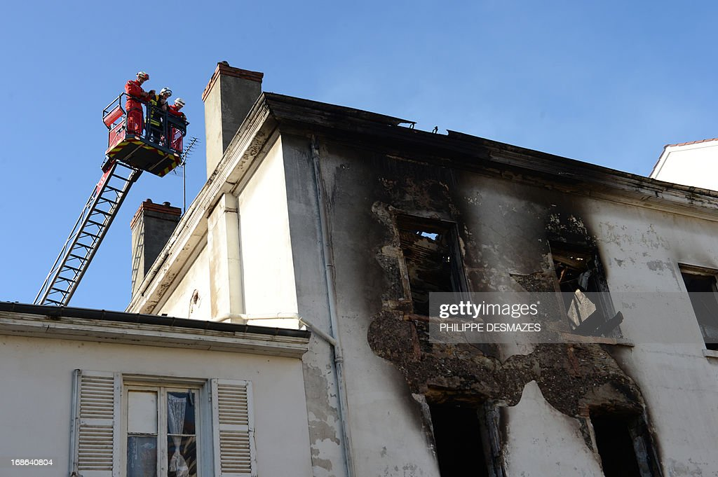 Firefighters stand above an abandoned factory that was housing nearly 300 Roma squatters, which went on fire overnight, killing at least three people, including a child, on May 13, 2013 in the southeastern city of Lyon. Up to seven people in all could have perished in the fire, which began shortly after midnight and completely destroyed the building, fire fighters and police said. Officials said two women and a child were confirmed dead. Local human rights activists said the building was mostly used by women and children.