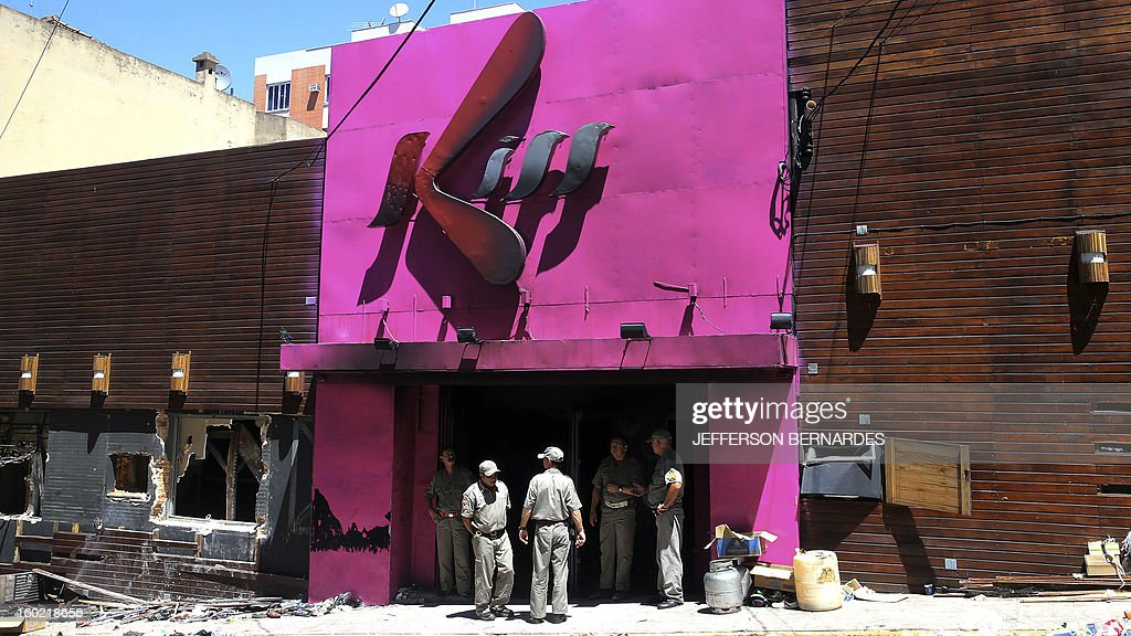 Firefighters stand at the burnt out entrance of the Kiss night club, on January 27, 2013 in Santa Maria. Brazilians were mourning the victims of a nightclub blaze in a small college town that left more than 230 people dead and over 100 injured, with many still fighting for their lives.