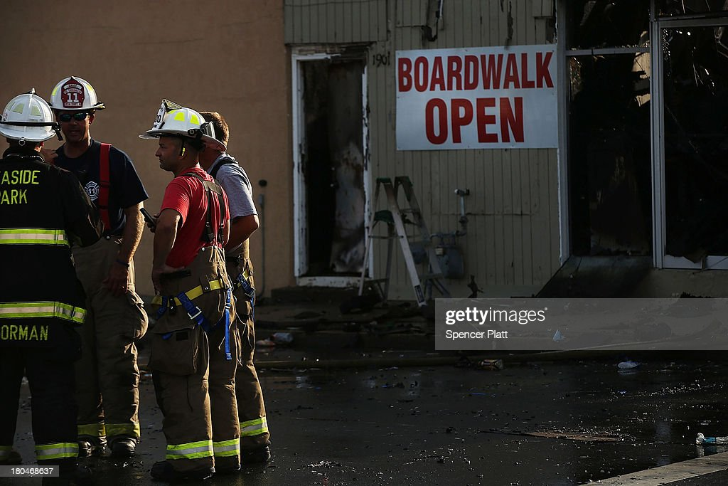Firefighters stand at the scene of a massive fire that destroyed dozens of businesses along an iconic Jersey shore boardwalk on September 13, 2013 in Seaside Heights, New Jersey. The 6-alarm fire began in a frozen custard stand on the recently rebuilt boardwalk around 2:00 p.m. on Thursday, September 12, and quickly spread in high winds. While there were no injuries reported, many businesses that had only recently re-opened after Hurricane Sandy were destroyed in the blaze.