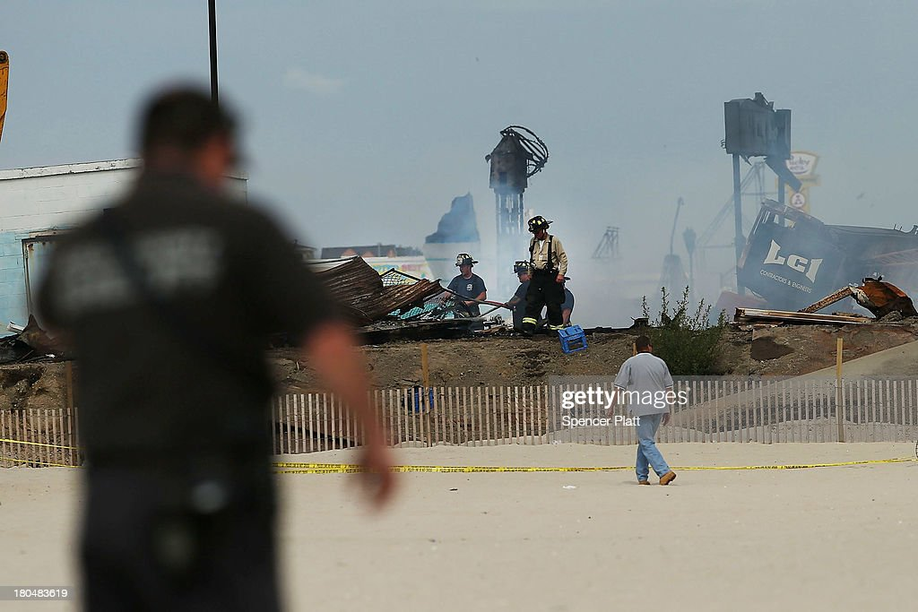 Firefighters stand at the scene of a massive fire that destroyed dozens of businesses along an iconic Jersey shore boardwalk on September 13, 2013 in Seaside Heights, New Jersey. The 6-alarm fire began in a frozen custard stand on the recently rebuilt boardwalk around 2:00 p.m. on September 12, and quickly spread in high winds. While there were no injuries reported, many businesses that had only recently re-opened after Hurricane Sandy, were destroyed in the blaze.