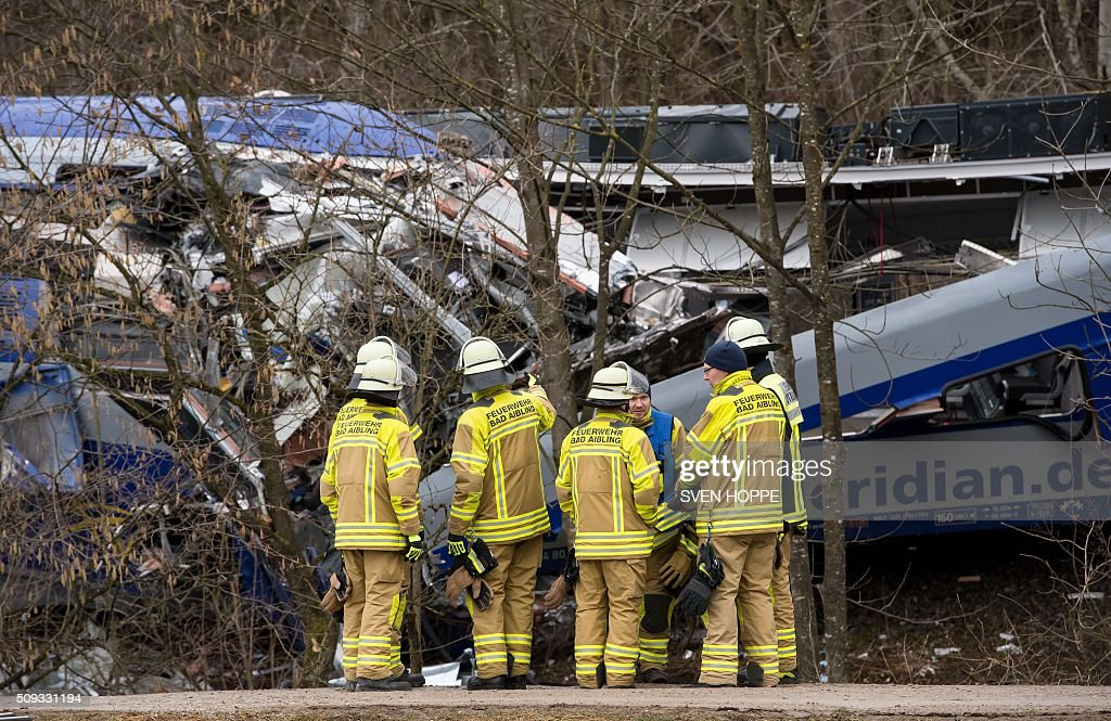 Firefighters stand at the site of a train accident near Bad Aibling, southern Germany, on February 10, 2016. Two Meridian commuter trains operated by Transdev on February 9, 2016 collided head-on near Bad Aibling, around 60 kilometres (40 miles) southeast of Munich, killing at least ten people and injuring around 100, police said. / AFP / dpa / Sven Hoppe / Germany OUT