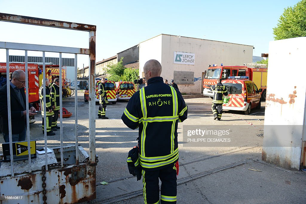 Firefighters stand at the site of an abandoned factory that was housing nearly 300 Roma squatters, which went on fire overnight, killing at least three people, including a child, on May 13, 2013 in the southeastern city of Lyon. Up to seven people in all could have perished in the fire, which began shortly after midnight and completely destroyed the building, fire fighters and police said. Officials said two women and a child were confirmed dead. Local human rights activists said the building was mostly used by women and children.
