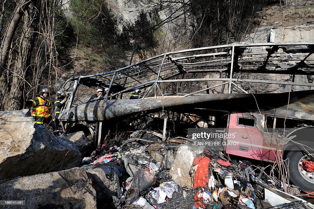 Firefighters stand by the wreckage of a bus transporting British citizens that crashed on April 16, 2013 near Bourg d'Oisans as they were leaving the French Alps resort of l'Alpe d'Huez. The accident killed at least one person, severely wounded three others, and slightly injured 21. In total, 53 people were aboard the bus, including two drivers.