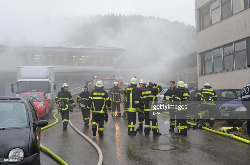 Firefighters stand in front of house with a workshop for handicapped people in Titisee- Neustadt, southern Germany on November 26, 2012. Fourteen people died after a fire broke out. AFP PHOTO / PATRICK SEEGER GERMANY OUT