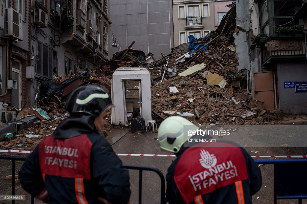 Firefighters stand in front of rubble after two buildings collapsed on a side street behind Istiklal street on February 12, 2016 in Istanbul, Turkey. Preliminary inspections reported that there was no one inside. Pedestrians near the building heard sounds from the buildings and realized they was about to collapse and were able to alert people on the street and inside, preventing a disaster.