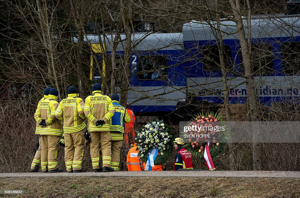 Firefighters stand in front of wreathes laid down at the site of a train accident near Bad Aibling, southern Germany, on February 10, 2016. Two Meridian commuter trains operated by Transdev on February 9, 2016 collided head-on near Bad Aibling, around 60 kilometres (40 miles) southeast of Munich, killing at least ten people and injuring around 100, police said. / AFP / dpa / Sven Hoppe / Germany OUT