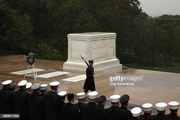Firefighters stand in the pouring rain ahead of a wreath laying ceremony at the Tomb of the Unknowns at Arlington National Cemetery October 1 2015 in...