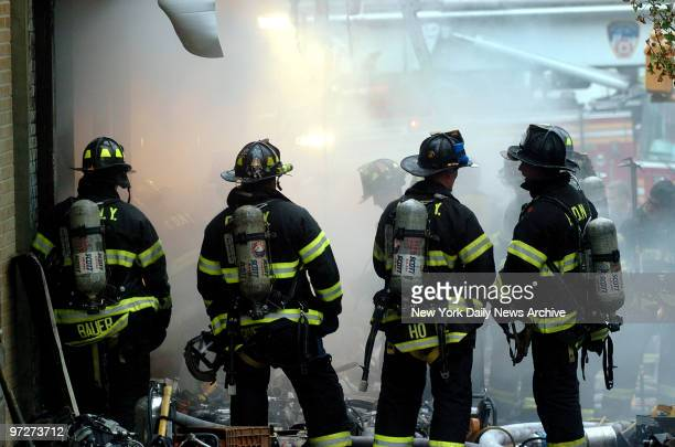 Firefighters stand in the rain at the scene of a fire at the corner of Walton and E Mount Eden Aves in the Bronx where five firefighters were trapped...