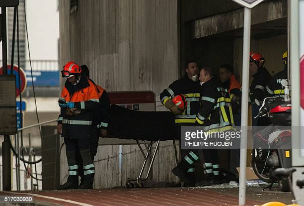 Firefighters stand near a stretcher carrying a body bag on March 23 2016 outside the Maalbeek metro station in Brussels one day after the attack that...