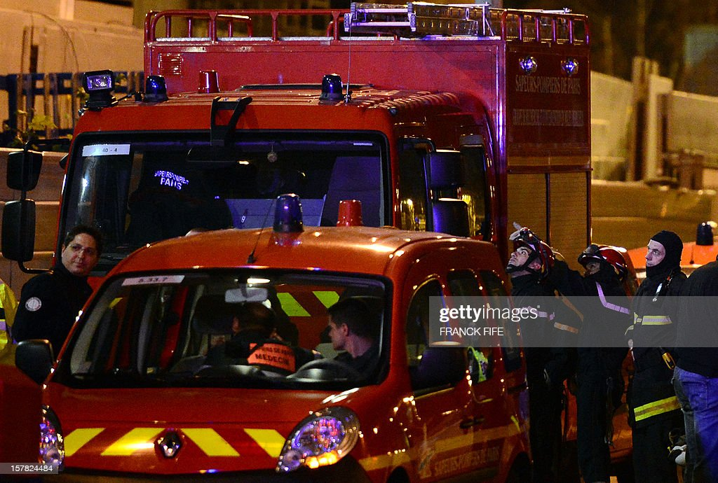 Firefighters stand next to vehicles as they work on the construction site of a shopping mall after a concrete slab collapsed on December 6, 2012 in Villeneuve-la-Garenne, near Paris. One worker died in the accident.