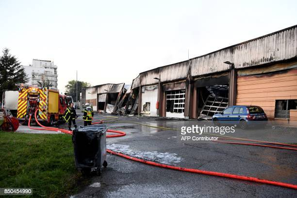 Firefighters stand on September 21 2017 in Grenoble eastern France beside a burntout garage which contained about fifty vehicles of the French...