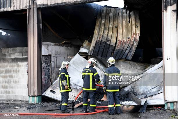 Firefighters stand on September 21 2017 in Grenoble eastern France in front of a burntout garage which contained about fifty vehicles of the French...