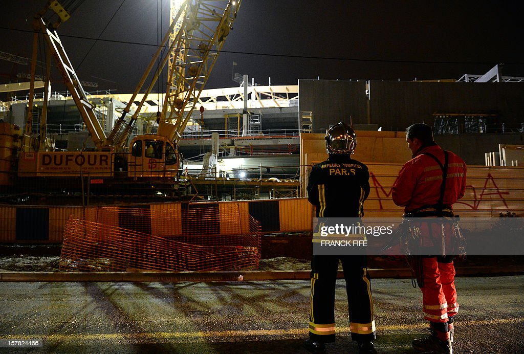 Firefighters stand on the construction site of a shopping mall after a concrete slab collapsed on December 6, 2012 in Villeneuve-la-Garenne, near Paris. One worker died in the accident.