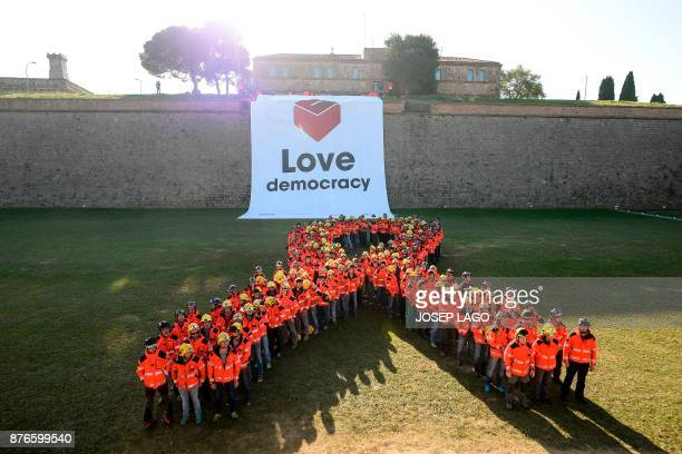 Firefighters stand to form the shape of a giant ribbon at the Montjuic Castle in Barcelona on November 20 2017 during a protest calling for the...